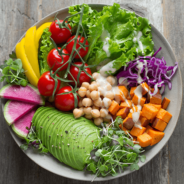 Healthy looking salad bowl with many fresh items and salad dressing